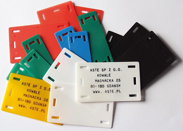 Rys. 2. Tabliczki Asteid firmy Aste – wykonane z poliamidu 6, służą do trwałego znakowania kabli i rur ziemnych oraz kabli i przewodów w instalacjach elektrycznych, energetycznych, telekomunikacyjnych i komputerowych. Sześć otworów montażowych pozwala na zamocowanie tabliczki wzdłuż lub w poprzek
